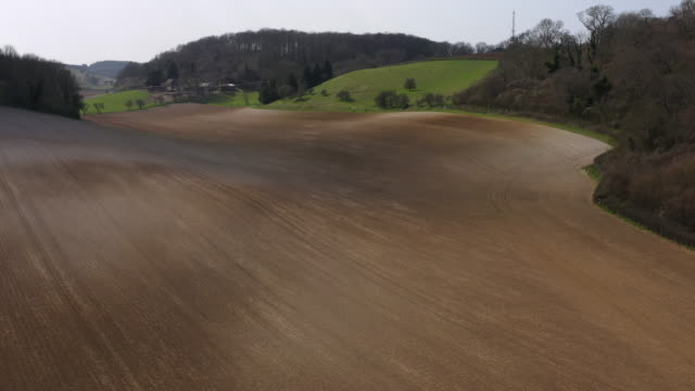aerial flying over plowed field, daytime - plough stock videos & royalty-free footage
