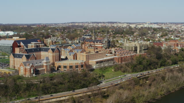 stockvideo's en b-roll-footage met aerial flying over potomac river looking at georgetown university dc - d day