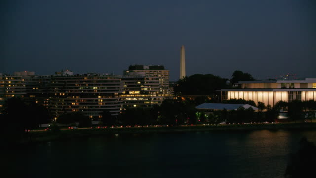 aerial flying over potomac river looking at washington dc at night - performing arts center stock videos & royalty-free footage