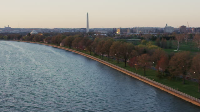 aerial flying over potomac river, with view of washington monument, sunset - potomac river stock-videos und b-roll-filmmaterial