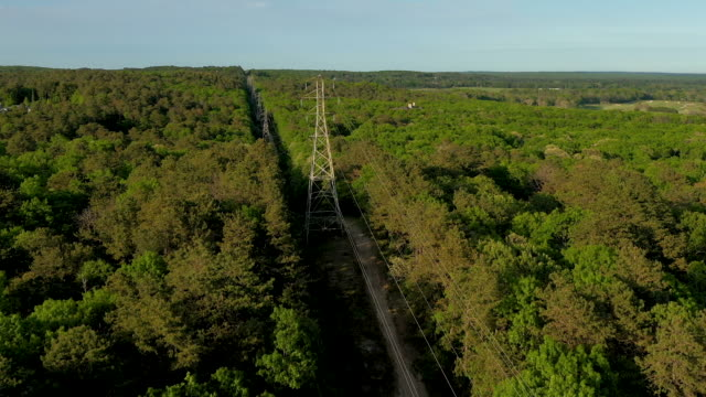 aerial flying over power lines in water mill ny, daytime - strom stock-videos und b-roll-filmmaterial
