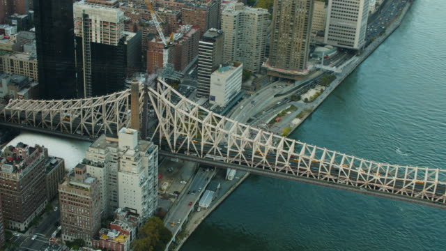 Aerial flying over Queensboro Bridge, Roosevelt Island, East River in NYC