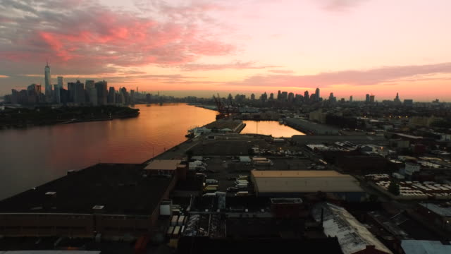 aerial flying over red hook brooklyn at sunrise towards manhattan - stimmungsvoller himmel stock-videos und b-roll-filmmaterial