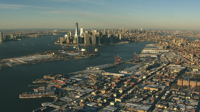 Aerial flying over Red Hook, Brooklyn towards south end of Manhattan covered in snow