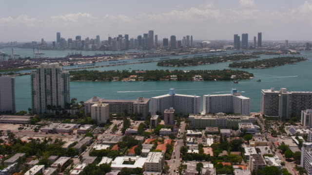 stockvideo's en b-roll-footage met aerial flying over residential area, downtown miami in distance, fl - macarthur causeway bridge