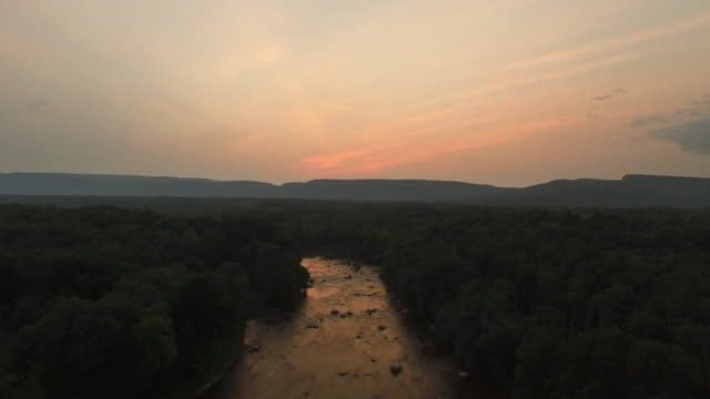 aerial flying over river and trees at sunset - ニューパルツ点の映像素材/bロール