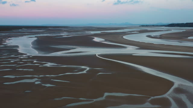 aerial flying over sand in estuary at low tide in north wales at sunset - twilight stock videos & royalty-free footage