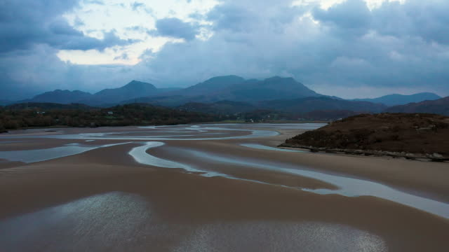 aerial flying over sand in estuary at low tide in north wales at sunset - low tide stock videos & royalty-free footage