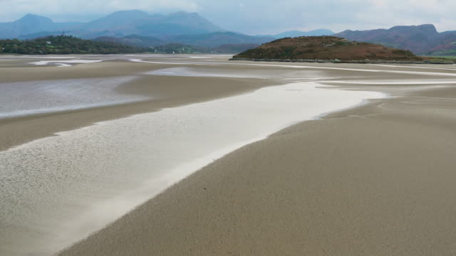 aerial flying over sand in estuary at low tide in north wales, sunset - beach stock videos & royalty-free footage