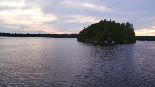 Aerial flying over small island in lake, Sunset