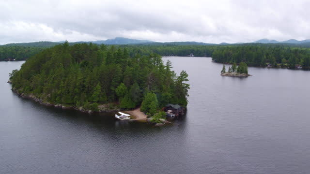 Aerial flying over small island in Saranac lake, afternoon