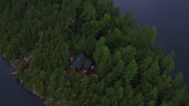 Aerial flying over small island in Saranac lake, late afternoon