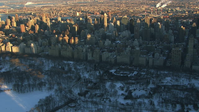 aerial flying over snow covered central park looking at 5th avenue, nyc - queens new york city stock videos & royalty-free footage
