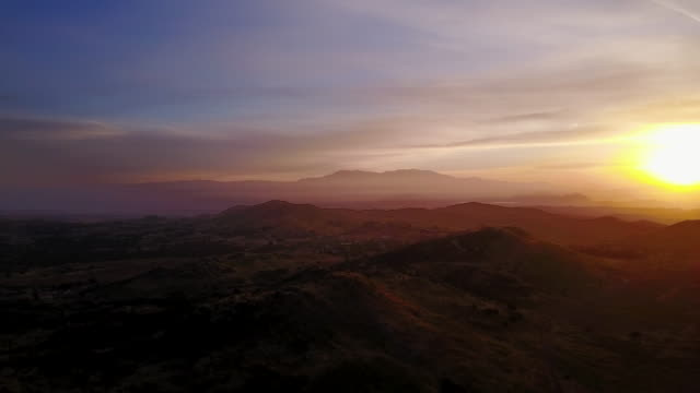 aerial flying over southern california hilly area at sunrise - riverside california stock videos and b-roll footage