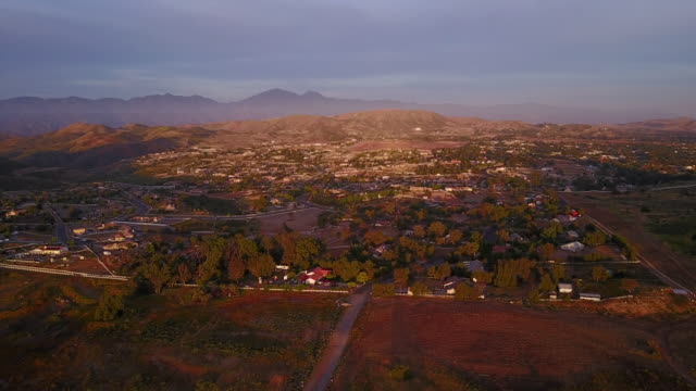 vídeos de stock, filmes e b-roll de aerial flying over southern california hilly residential area at sunrise - califórnia