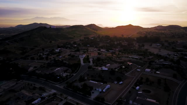 Aerial flying over Southern California hilly residential area at sunrise