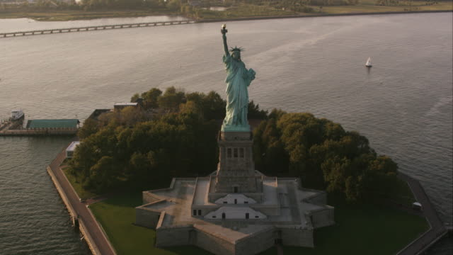 Aerial flying over Statue of Liberty at the end of the day, NYC