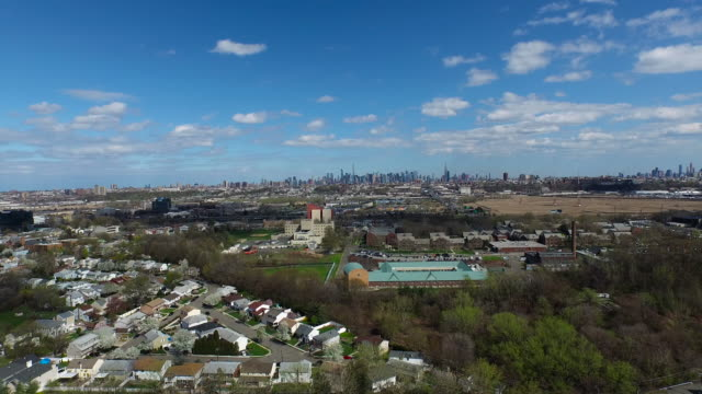 aerial flying over suburban and industrial area, manhattan in the distance - new jersey stock videos & royalty-free footage