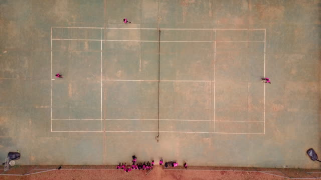 aerial flying over tennis court with children playing tennis, congo africa daytime - コート点の映像素材/bロール