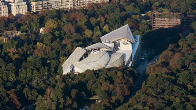 aerial flying over the bois de boulogne and fondation louis vuitton in paris france - museum stock videos & royalty-free footage