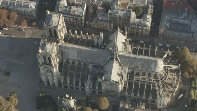 aerial flying over the cathédrale notre-dame, in paris france daytime - notre dame de paris stock videos and b-roll footage