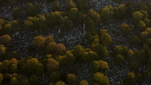 vidéos et rushes de aerial flying over the cimetière de montmartre in paris france, sunset - cimetière