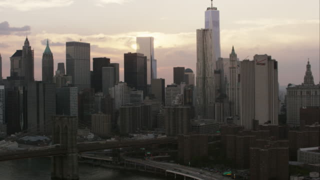 aerial flying over the east river past manhattan bridge, over the brooklyn bridge at sunset in nyc - brooklyn bridge stock-videos und b-roll-filmmaterial