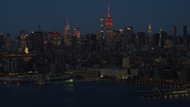 Aerial flying over the Hudson River, view of Midtown Manhattan, evening NYC