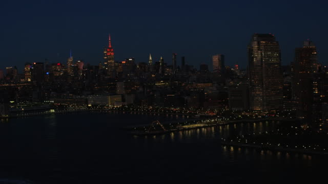 Aerial flying over the Hudson River, view of Midtown Manhattan, night NYC