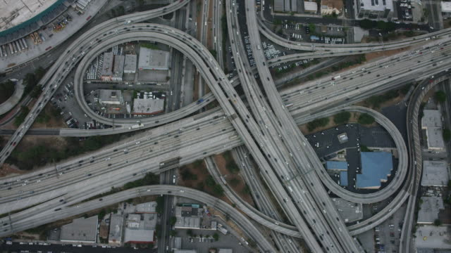 Aerial flying over the Interstate 110 and 10 interchange in Los Angeles California looking directly down on the cloverleaf, commuter traffic on the expressways, camera zooms in to tight shot of the freeways intersecting, LA, CA, USA