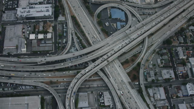 aerial flying over the interstate 110 and 10 interchange in los angeles california looking directly down on the cloverleaf, commuter traffic on the expressways, camera zooms in to tight shot of the freeways intersecting, la, ca, usa - motorway junction stock videos & royalty-free footage
