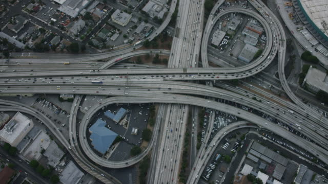 aerial flying over the interstate 110 and 10 interchange in los angeles california looking directly down on the cloverleaf, commuter traffic on the expressways, camera zooms in to tight shot of the freeways intersecting, la, ca, usa - autostrada interstatale americana video stock e b–roll