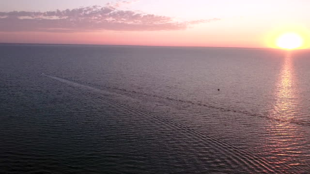 aerial flying over the ocean following a boat as it goes out towers the open water at sunrise - small boat stock videos & royalty-free footage