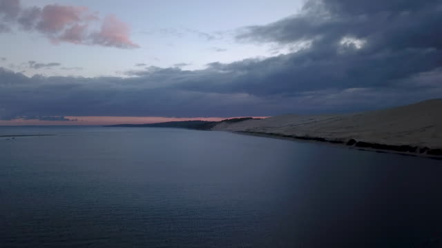 aerial flying over the ocean towards the dune of pilat at sunrise - arcachon stock videos & royalty-free footage