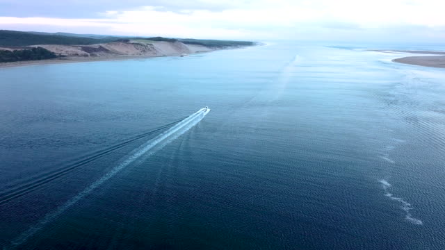 aerial flying over the ocean towards the dune of pilat looking at motor boat in water at sunrise - arcachon stock videos & royalty-free footage