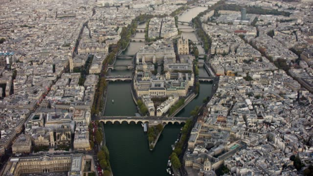 aerial flying over the seine river towards île de la cité in paris france at sunset - geografische lage stock-videos und b-roll-filmmaterial