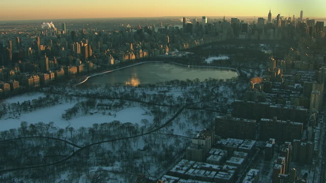 aerial flying over upper west side in manhattan looking south at central park and new york city covered in snow - central park manhattan stock videos & royalty-free footage