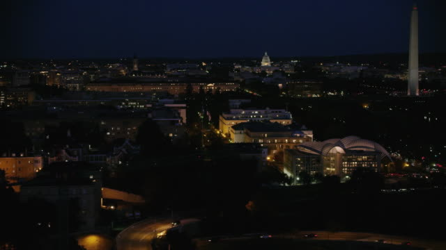 Aerial flying over Washington DC at night with lights on