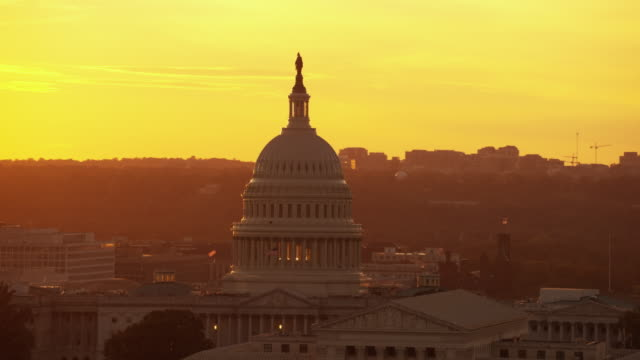 aerial flying over washington dc, view of united states capitol, sunset usa - governo video stock e b–roll