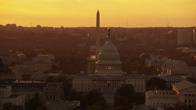 Aerial flying over Washington DC, view of United States Capitol, sunset USA