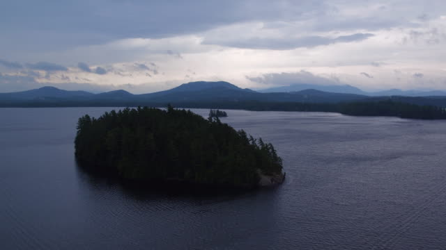 Aerial flying over water and small island on Saranac lake, cloudy afternoon