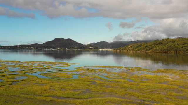 aerial flying over water in estuary at high tide in north wales, daytime - tide stock videos & royalty-free footage