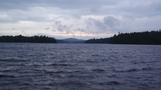 Aerial flying over water of Saranac lake, afternoon