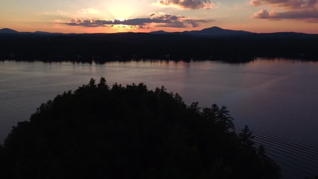 Aerial flying over water of Saranac lake and over small island at sunset