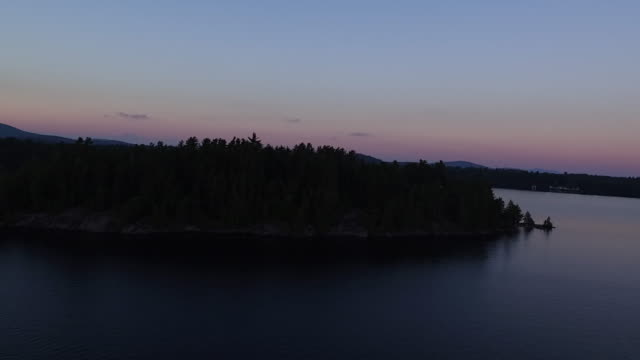Aerial flying over water of Saranac lake around small island at sunset