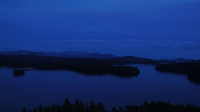 Aerial flying over water of Saranac lake at sunset