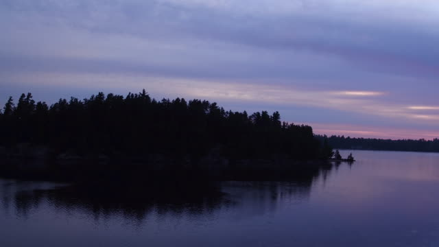 Aerial flying over water of Saranac lake away from small island at Sunrise