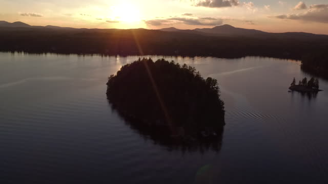 Aerial flying over water of Saranac lake back away from small island at sunset