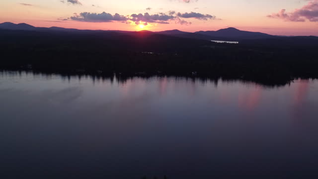 Aerial flying over water of Saranac lake back over small island at sunset