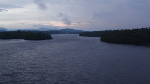Aerial flying over water of Saranac lake, cloudy afternoon